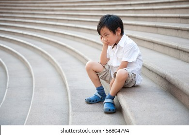 Unhappy schoolboy sitting on the stairs