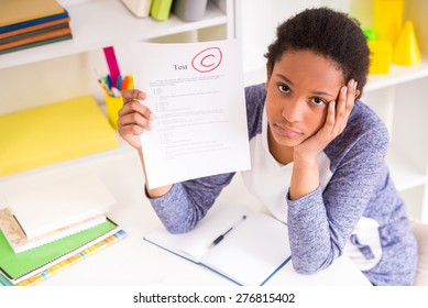 Unhappy schoolgirl sitting at the table and  showing  bad test results on colorful background.