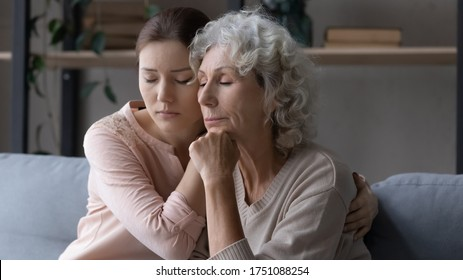 Unhappy senior Caucasian mother and grownup daughter sit on sofa hugging make peace reconcile, caring adult girl comfort caress sad mature 60s mom, show support and love, family unity concept