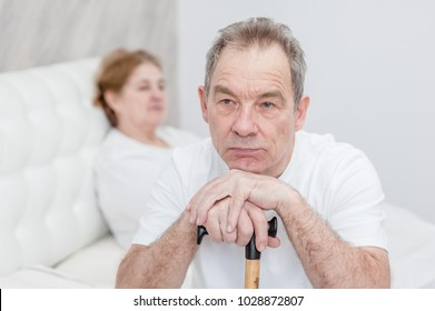 unhappy senior couple sitting on bed