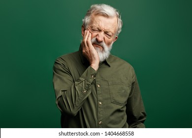 unhappy senior man with closed eyes holding cheek, man suffers from toothache, senior man problems with teeth. tooth care. health concept , isolated green background, strong pain in tooth. tooth decay