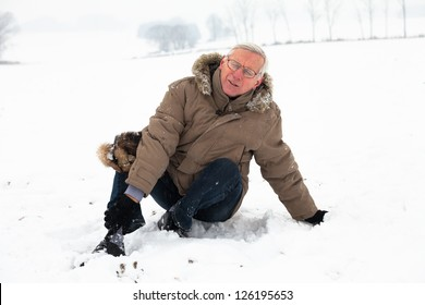 Unhappy senior man with injured painful leg on snow.