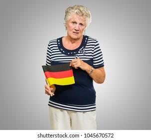 Unhappy Senior Woman Holding Germany Flag On Grey Background