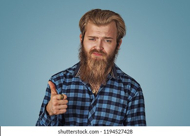 Unhappy skeptical doubtful man showing giving thumbs up hand gesture. Hipster male with beard in blue plaid checkered shirt  Isolated on blue studio Background. Negative face expression, human emotion