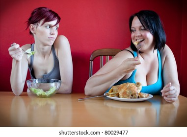 Unhappy skinny woman eating a few leaves of lettuce while the happy overweight woman is eating a whole chicken. Selective focus.