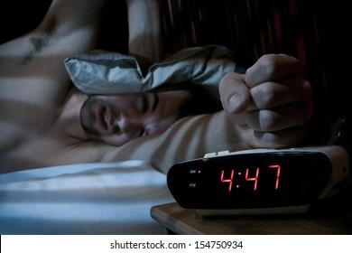 Unhappy sleeping man smashing the alarm clock in the morning (very early).