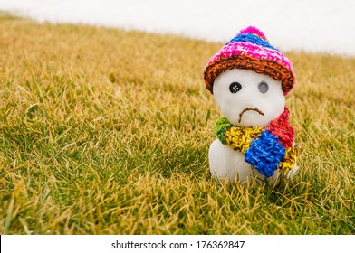 Unhappy snowman melting on green grass with white snow in the background