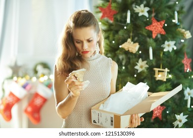 unhappy stylish woman near Christmas tree looking at a broken dish from the parcel