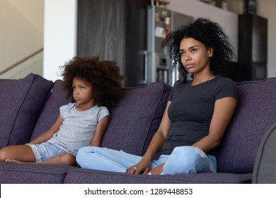 Unhappy sulky african child girl and annoyed mother sitting on sofa not talking after fight, stubborn mixed race kid daughter and mom ignore each other upset by quarrel, black family conflict concept