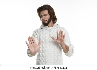 Unhappy tensed young European man with stubble keeping eyes closed and reaching out both hands, making stop gesture, having painful facial expression. Body language and negative human emotions