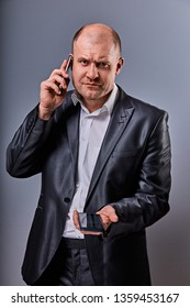 Unhappy tired angry business man talking on mobile phone and holding in hand one more phone in office suit on grey studio background. Closeup portrait