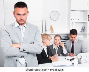 Unhappy and tired man standing at office on background with working colleagues