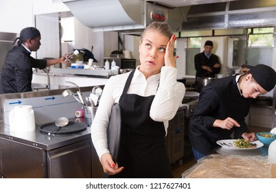 Unhappy and tired young waitress waiting ordered dishes in restaurant kitchen