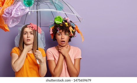 Unhappy two diverse women volunteers activists suffer from suffocation, smell stinky trash, stand under polythene umbrella, collect plastic garbage, touch throats, pose against purple studio wall