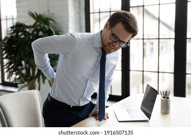 Unhappy unwell male employee suffer sitting in incorrect posture at desk in office, have backache or muscular spasm. Unhealthy man worker struggle with back muscle strain. Sedentary life concept.