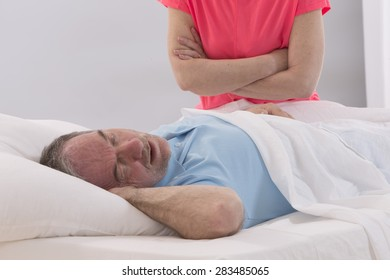 Unhappy woman because her snoring husband in bedroom.
