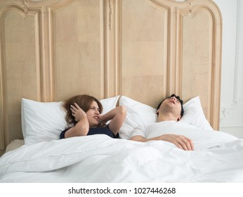 Unhappy woman covering ears while man snoring in bed at home. Family, bedtime and couple concept.