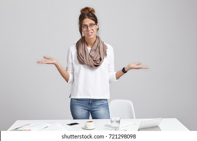 Unhappy woman frowns face in displaesure, shrug shoulders, has bad mood, stands at office table, makes mistake in annual report, should do calculation from beginning, look desperatedly and upset