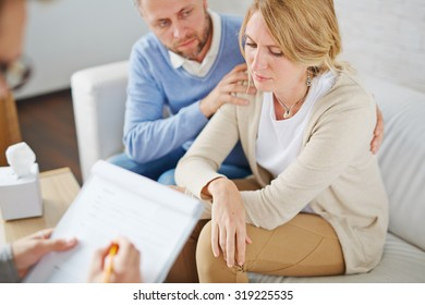 Unhappy woman and her anxious husband visiting psychologist together