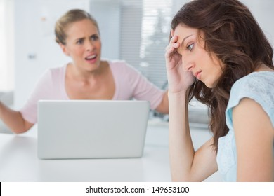 Unhappy woman in her kitchen thinking while her friend is interrogating her