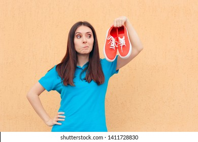 Unhappy Woman Holding a Pair of Red Sport Shoes. Customer checking gumshoes displeased with the quality