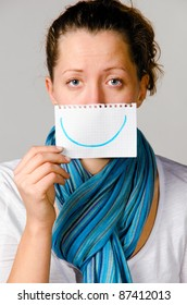 unhappy woman is holding paper with drawn smile