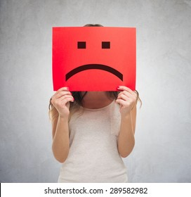 Unhappy woman holding a sad emoticon in front of his face