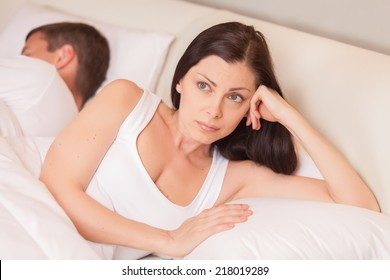 unhappy woman lying in bed stressed. couple having problem while man sleeping