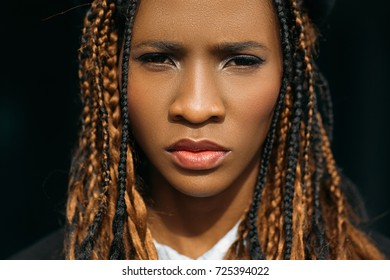 Unhappy woman portrait. Sad black female. Grumpy young girl on dark background, unimpressed facial expression, melancholy concept