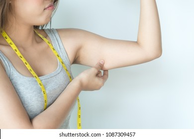 Unhappy woman pulling her upper arm and displeased with fat excess cellulite on her arm.