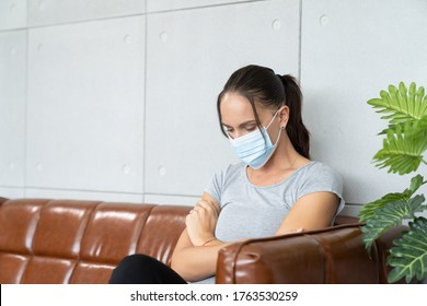 Unhappy woman quarantined wearing face mask and covered face with her hand feeling despair sitting on the sofa while feeling stressed, worried, sad during to coronavirus, or COVID 19 outbreak