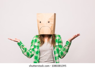 Unhappy woman with sad emoticon in front of paper bag on her head on white background