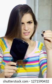 unhappy woman seeing hair in brush