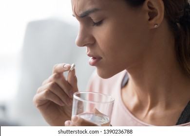 Unhappy woman side view holds tablet and glass of water close up image, abortion pill way end early pregnancy, unhealthy girl sad upset face expressions taking painkiller to reduce sharp ache concept