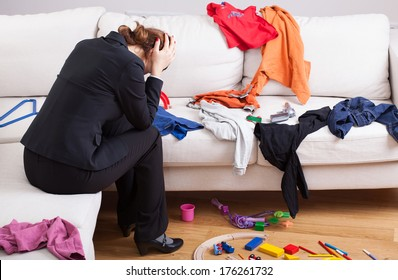 An unhappy woman sitting on a sofa in a messy living room