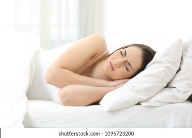 Unhappy woman sleeping on an uncomfortable mattress at home