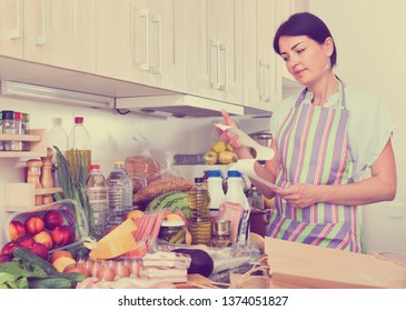 Unhappy woman is standing with check and is sading because of the prices of food at home.