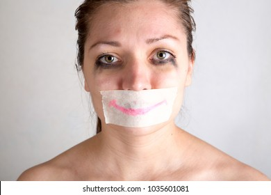 Unhappy woman with wrapping her mouth by adhesive tape painted smile.