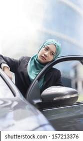 Unhappy women with scarf felling depressed not knowing the problem of her car