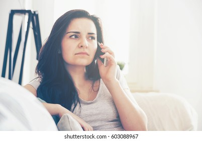 Unhappy worried woman talking on phone while sitting on sofa at home