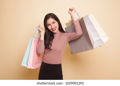 Unhappy  young Asian woman with shopping bags and credit card on beige background