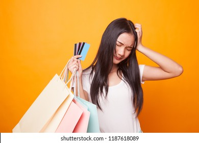 Unhappy  young Asian woman with shopping bags and credit card on bright yellow background