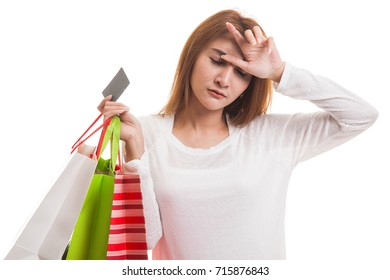 Unhappy  young Asian woman with shopping bags and credit card  isolated on white background