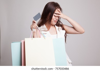 Unhappy  young Asian woman with shopping bags and credit card on gray background