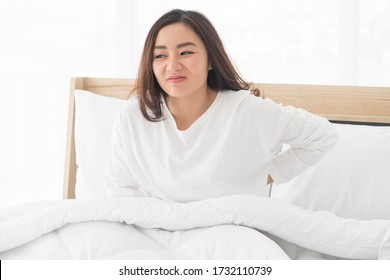 Unhappy Young Asian woman suffering stomach aches from abdominal pain during the period of PMS and menstruation. Painful menstruation. Inflammation and Bladder Infection while sitting on bed at home.