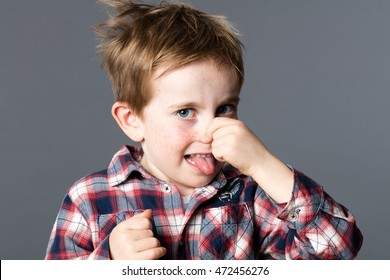 unhappy young boy pinching his nose for sign of bad odor, sticking out his tongue for humor and mischievous childhood, grey background