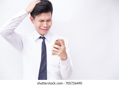 Unhappy young business man being sad as reading message at smartphone in his hand with white background and copyspace.