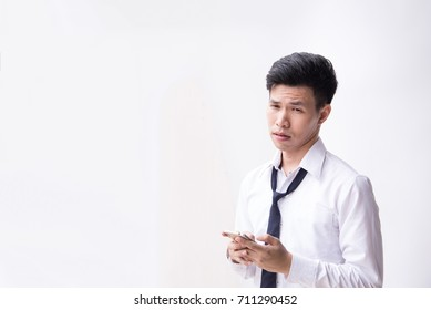 Unhappy young business man being sad after reading message at smartphone in his hand with white background and copyspace.