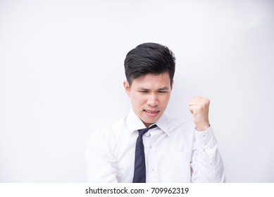 Unhappy young business man think and fist raised with white background and copyspace.