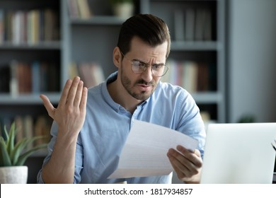 Unhappy young Caucasian man in glasses sit at desk work at laptop read bad unexpected news in postal correspondence. Angry male frustrated by dismissal or eviction notice in paperwork letter.